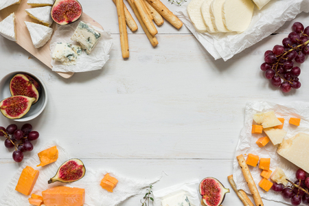 各種類型的奶酪,用木製的白色桌子上的水果與副本空間。頂視圖。