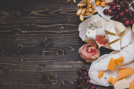 Various types of cheese with fruits and snacks on the wooden dark table with copy space. Top view background. Stockfoto