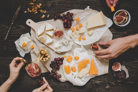 Eating different kinds of cheeses with fruits and snacks on the wooden dark table. Top view.
