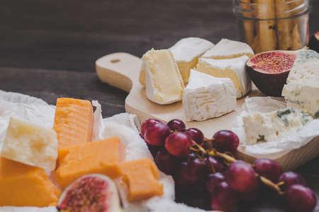 各種類型的水果和堅果在木製的黑色桌子上的奶酪。選擇性的焦點。