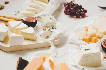 各種類型的奶酪,木製的白色桌子上的水果。選擇性的焦點。