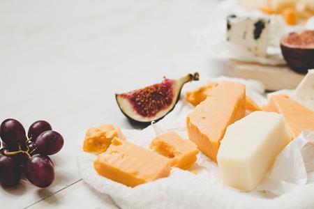 Différents types de fromage avec des fruits sur la table en bois blanche avec espace de copie. Mise au point sélective