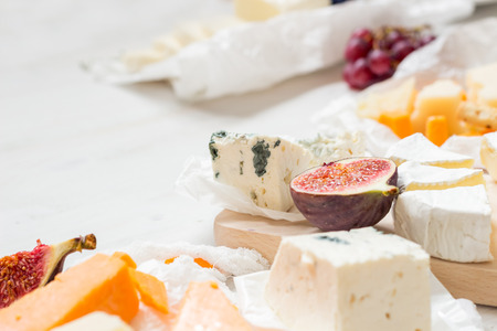 Various types of cheese with fruits on the wooden white table with copy space. Selective focus.