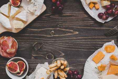 Cheese selection with fruits and snacks on the wooden dark table with copy space. Top view background.