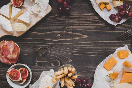 Sélection de fromages avec des fruits et des collations sur la table en bois sombre avec espace copie. Fond de vue de dessus.