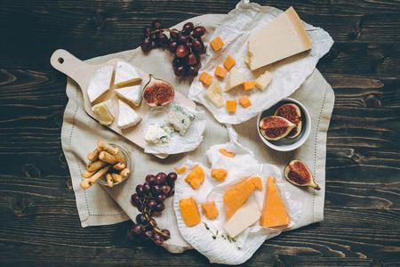 水果和小吃在木製的黑色桌子上的奶酪選擇。頂視圖。