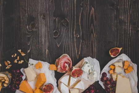 Various types of cheese with fruits and snacks on the wooden dark table with copy space. Top view background. Фото со стока