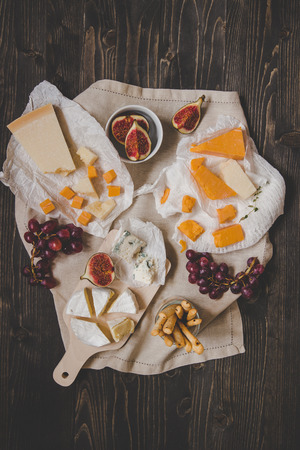 Different kinds of cheeses with fruits and snacks on the wooden dark table. Top view. Фото со стока