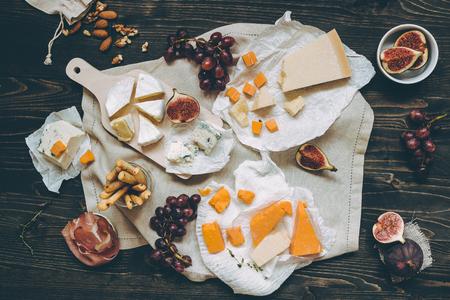 Différents types de fromages avec des fruits et des collations sur la table en bois sombre. Vue de dessus