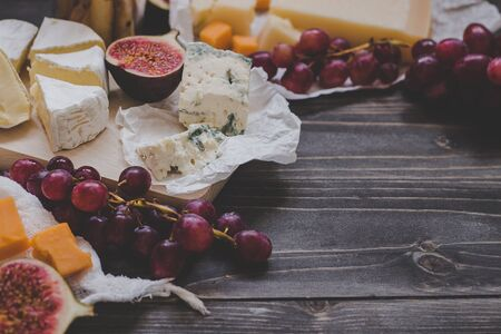Various types of cheese with fruits and nuts on the wooden dark table. Selective focus.