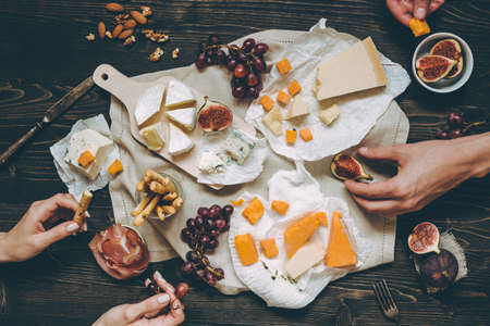 Eating various types of cheese with fruits and snacks on the wooden dark table. Top view.