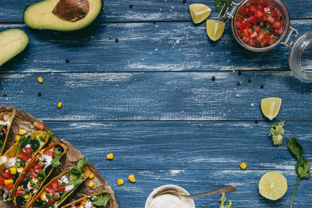 Mexican tacos with salsa and avocado on the wooden blue background, top view. Copy space Фото со стока