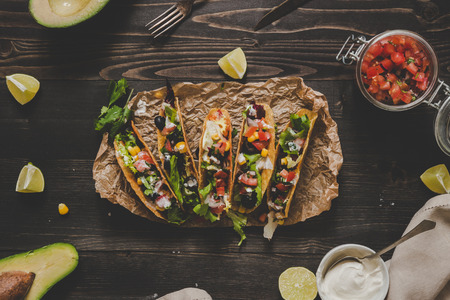 Mexican tacos with salsa and avocado on the wooden background, top view.