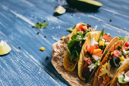 木製の青い背景に野菜とメキシコのタコス、クローズアップ。コピースペースを使用した選択的フォーカス