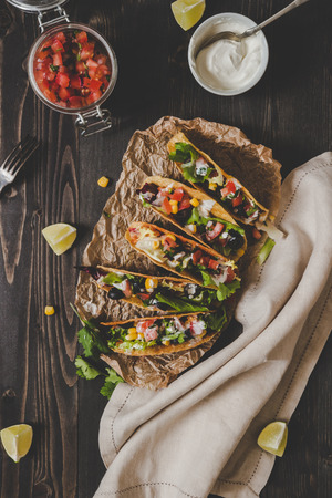 Mexican vegetarian tacos with salsa and avocado on the wooden background, top view. Copy space.
