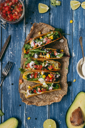 Mexican tacos with salsa and avocado on the wooden blue background, top view. Фото со стока