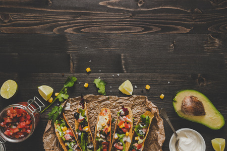 Mexican tacos with vegetables, salsa and avocado on the wooden background, top view. Copy space