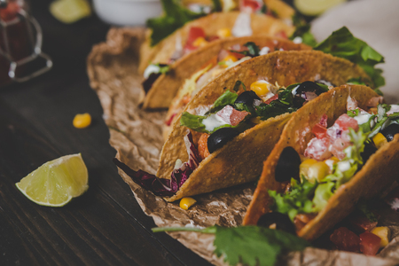 Mexican tacos with vegetables on the wooden background, close up. Selective focus Фото со стока