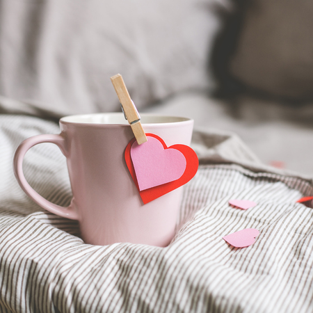 Valentines day background. Pink mug with hearts on the bed. Selective focus. Фото со стока