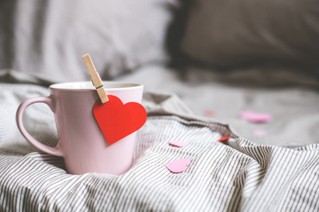 Valentines day background with copy space. Pink mug with heart on the bed. Selective focus. Фото со стока