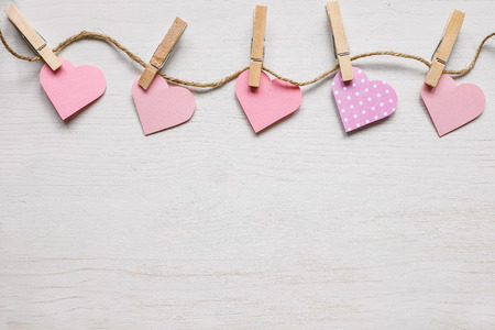 Valentines day background. Pink paper hearts on the wooden background. Copy space.