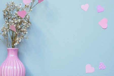 flowers in vase with pink paper hearts on the blue background. Copy space. Фото со стока