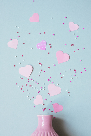 pink paper hearts with vase on the blue background. Top view.