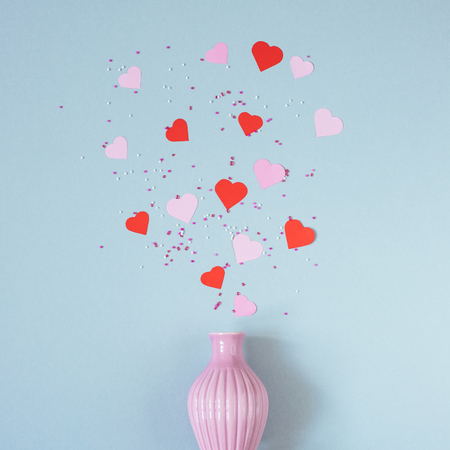 pink and red paper hearts with vase on the blue background. Top view.