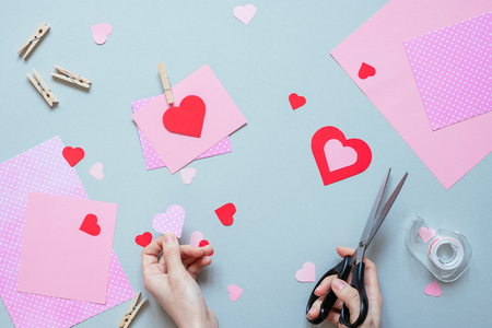 Valentines day background. Hands making Valentine card with heart and on the blue background.