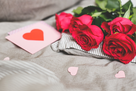 Romantic background with copy space. Beautiful roses and Valentine card with heart. Selective focus.