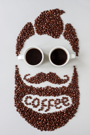 Coffee concept. Bearded hipster man made of coffee beans with glasses made of cups of coffee. Фото со стока