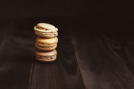 Chocolate and vanilla macaroons on the wooden table, with copy space. Фото со стока