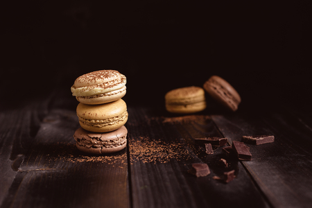 Delicious chocolate macaroons on the wooden table, with copy space.