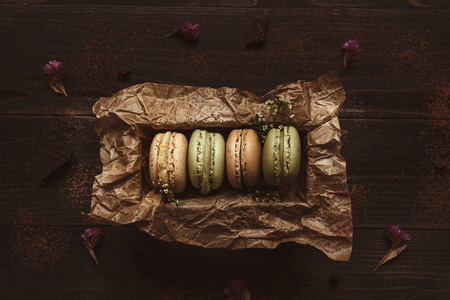 Delicious macaroons in gift box on the wooden table, top view. Фото со стока