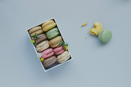 Gift box with delicious macaroons on the light blue background, top view. Фото со стока