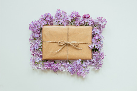 Cute gift box wrapped with craft paper and lilac flowers top view. Gift for any holiday.