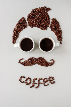 Man with mustache made of coffee beans and with glasses made of cups of coffee.
