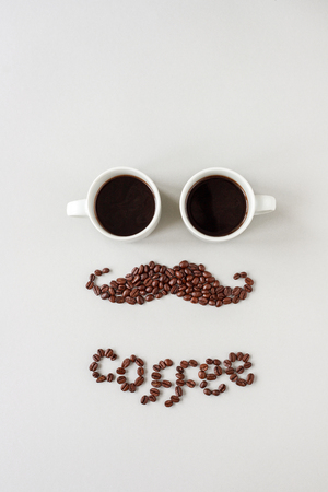 Mustache made of coffee beans with glasses made of cups of coffee.