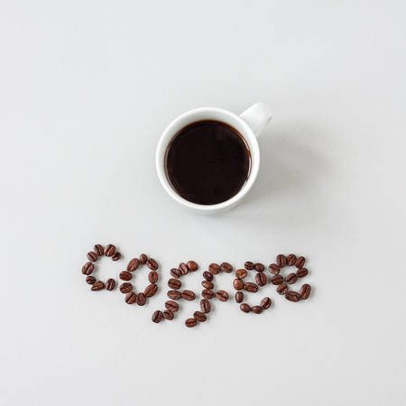 Coffee word made of coffee beans and cup of coffee, top view. Фото со стока