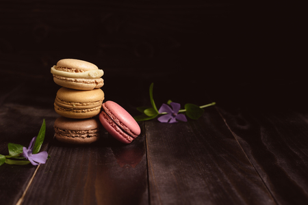 Delicious macaroons on the wooden table, with copy space.