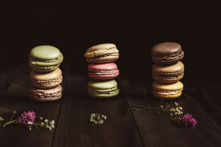 Delicious french dessert. Colorful macaroons on the wooden table.
