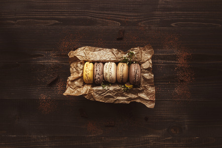 Delicious macaroons in gift box on the wooden table, top view. 版權商用圖片