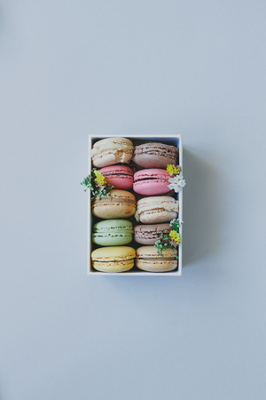 Cute gift box with delicious colorful macaroons on the light blue background, top view.