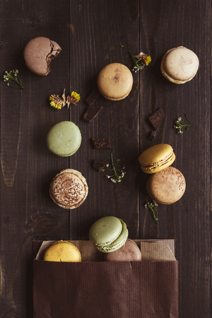 Sweet background. Delicious macaroons on the wooden table, top view.