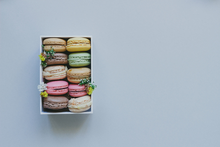 Gift box with delicious macaroons on the light blue background, top view. Copy space.