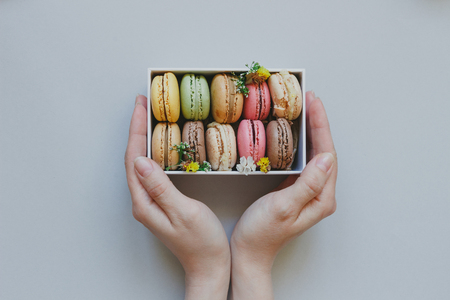 Hands holding gift box with delicious macaroons on the light blue background, top view.