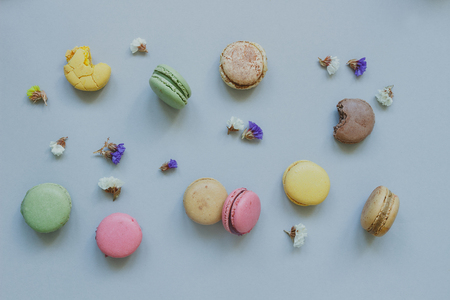 Sweet background. Delicious colorful macaroons on the light blue background, top view.
