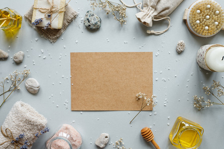 Spa composition. Craft paper with various products for spa treatments on rustic wooden background. Copy space