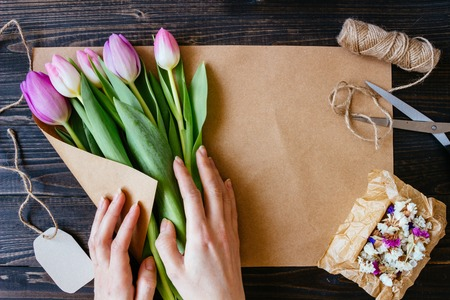 Florist preparing bouquet of fresh beautiful tulips on the wooden table