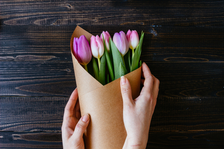 Hands holding bouquet of fresh beautiful tulips on the wooden table.